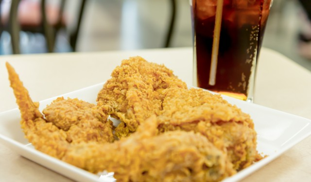 Crispy fried chicken with glass of cola closeup