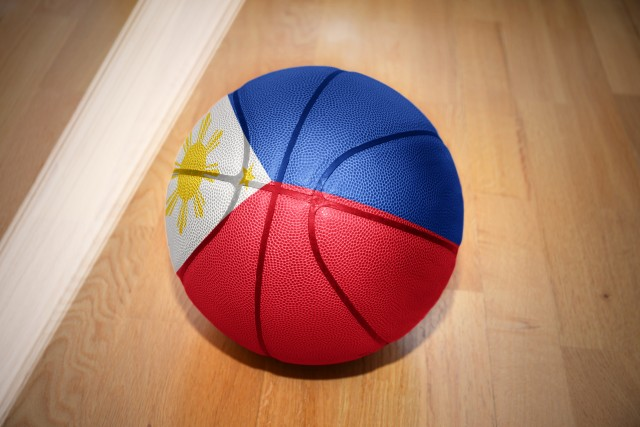 basketball ball with the national flag of philippines lying on the floor near the white line