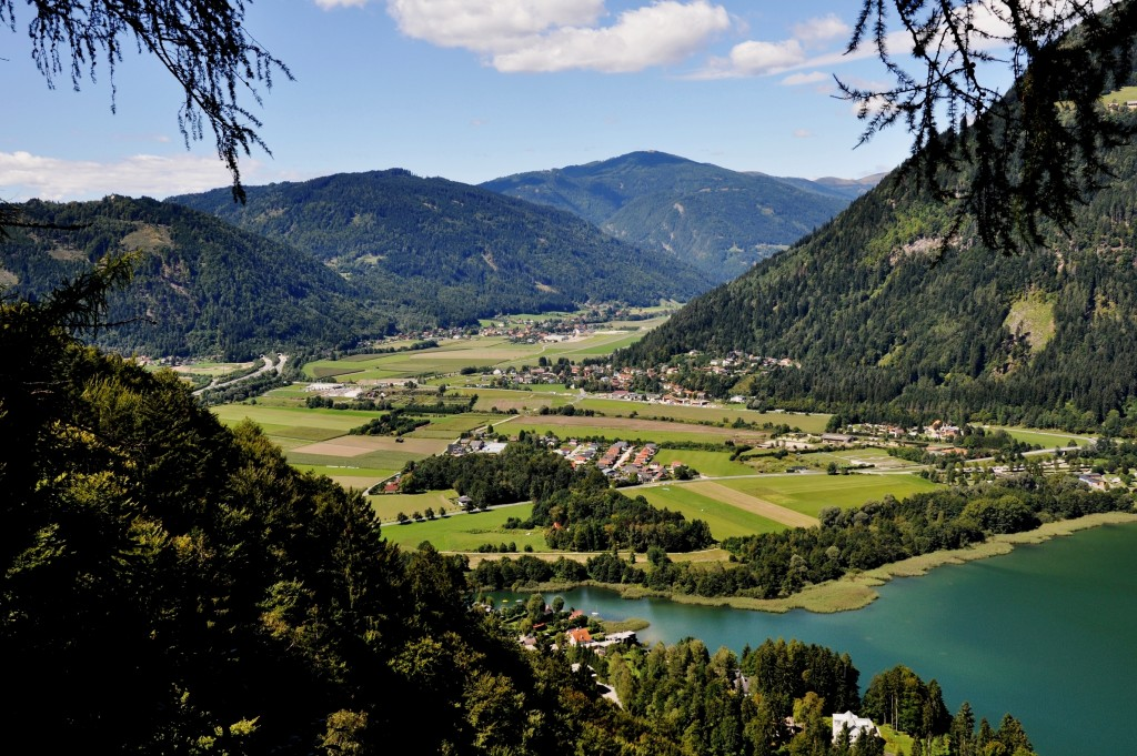 Panoramic view to Carinthia, Austria. A part of Lake Oaaiach situated next to meadows and fields.