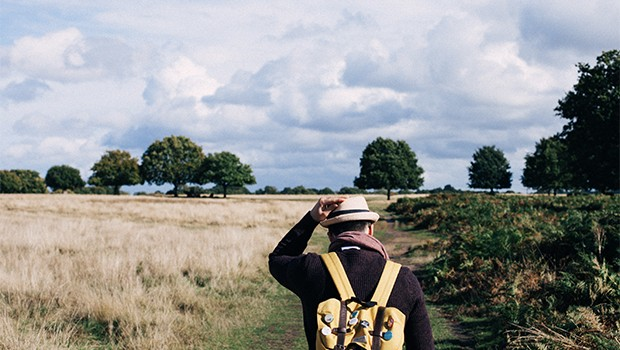 Main with backpack walking through field