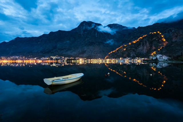 The evening view over the bay towards Kotor's old town with the fortress lit up