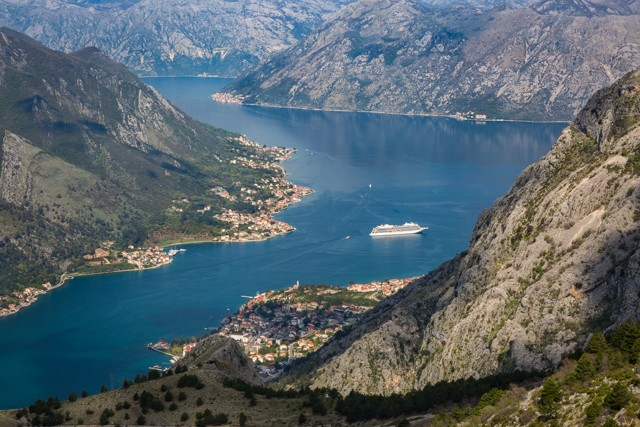 A cruise ships idles in the Bay of Kotor