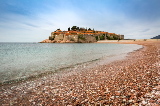 A sweeping stretch of one of Sveti Stefan's pebbled beaches
