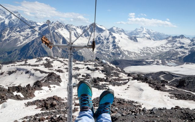 Feet in running shoes on the background of snow-covered mountain landscape, view from the mountain cable car