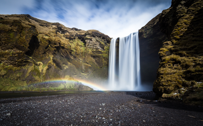 Sunlight creates a rainbow in the spray of Skogafoss, Iceland